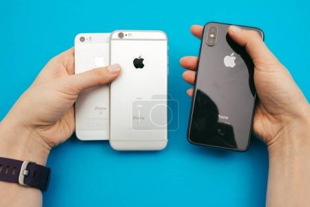 Holding in hands a new Apple iPphone X, iPhone SE and iPhone 6S
