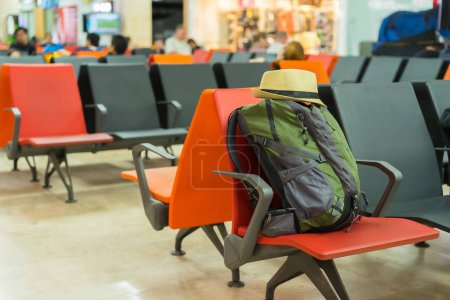 Photo for Tourist backpack and hat on chair in airport. - Royalty Free Image