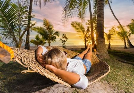 Photo for Woman relaxing on hammock at sunset on the beach. Vacation concept. - Royalty Free Image