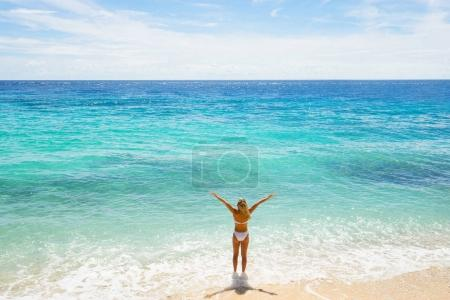 Photo for Happy young woman in white swimwear with raised hands on the beach. Back view. - Royalty Free Image