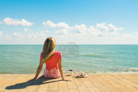 Woman on pier with coffee cup. Shoes off.  Beautiful sea and blue sky on background.