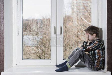 Photo pour Jeune garçon assis seul dans la fenêtre de pleurer et de cacher son visage dans les mains. - image libre de droit