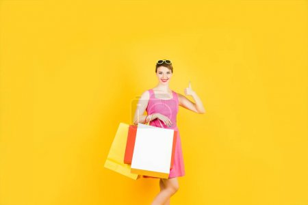 Photo for Happy woman showing good (big thumb up) and holding shopping bags in another hand. Colorful portrait in studio. - Royalty Free Image
