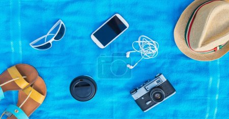 Photo for Smartphone, sunglasses, earphones, hat, shoes, cup of coffee and camera on blue towel. - Royalty Free Image