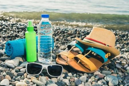 Foto de Concepto de vacaciones. Esencial en la playa del mar. Botella de agua, toalla, sombrero, zapatos de mujer, gafas de sol y sol había protegido crema. Tonificada de color. - Imagen libre de derechos