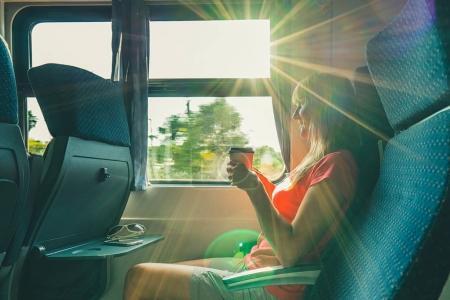 Photo pour J'aime voyager. Jeune jolie femme voyageant en train, assise près de la fenêtre et buvant du café . - image libre de droit