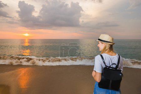 Photo pour Touristique avec sac à dos sur la plage et jouissant de coucher du soleil. Concept de voyage. - image libre de droit