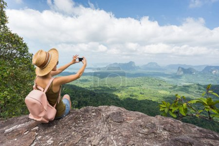 Photo for Tourist taking picture on her smartphone from top of mountain. Woamn in hat and with backpack sitting on rock. Travel concept. - Royalty Free Image