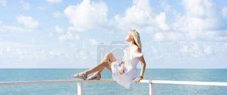 Young beautiful woman in white dress sitting on the pier and relaxing with blue sky and sea background. Banner background.