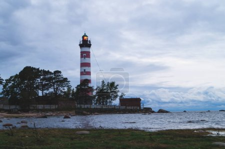Photo for High lighthouse shines near the shore at sunset. beacon at evening - Royalty Free Image