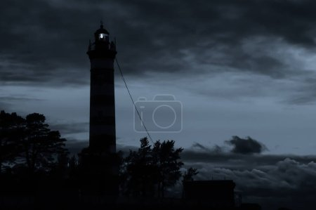 Photo for Lighthouse tower shines in the dark with a dramatic sky. silhouette of glowing beacon in darkness - Royalty Free Image