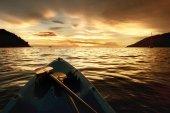 Kayak bow at sunset sea backdrop