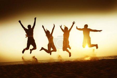 Photo pour Quatre amis heureux s'amusent et sautent à la plage du coucher du soleil - image libre de droit