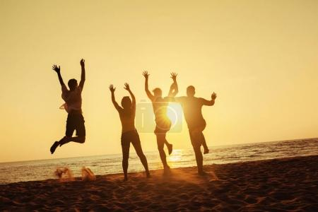 Photo for Group of four friends having fun, run and jump on sunset beach. Sea trave holidays concept. Space for text - Royalty Free Image