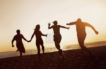 Photo for Group of four friends runs to sunset sea. Beach travel silhouettes concept - Royalty Free Image