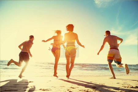 Photo for Beach holidays concept with four running friends to the sea - Royalty Free Image