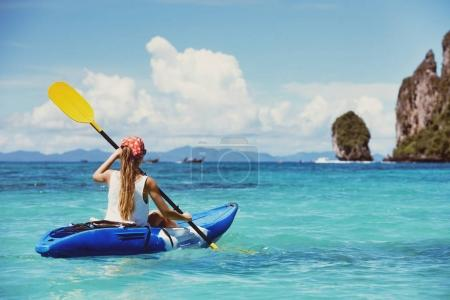 Photo for Girl on single kayak or canoe swims at tropical sea bay. Travel or kayaking concept - Royalty Free Image