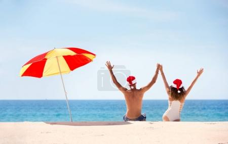 Photo for Happy couple with raised hands having fun in Santas hats near beach umbrella. New year or christmas tropical concept - Royalty Free Image