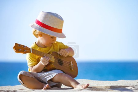 Photo pour Pretty kid plays on ukulele or small guitar at white sandy beach with blue water - image libre de droit