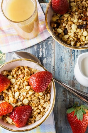 Photo for Healthy breakfast with  muesli, berries, fresh fruit juice, jug of milk, flat lay, vertical - Royalty Free Image