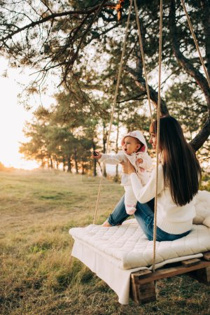 Photo for Mom and baby daughter on swing in park - Royalty Free Image