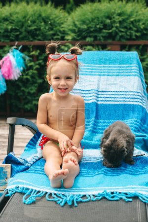 Photo for Beautiful little girl and cat on chair near pool - Royalty Free Image