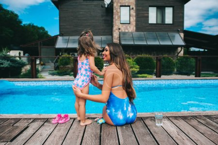 mother and daughter near pool