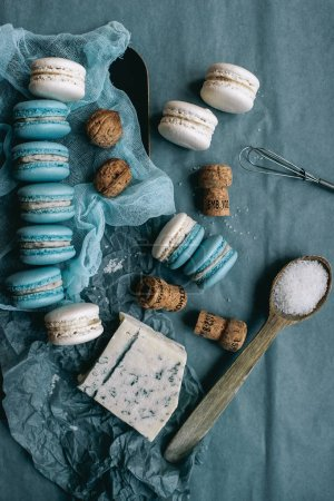 Photo for Sweet French macaroons, cheese, bowl with nuts, wooden corks, top view - Royalty Free Image