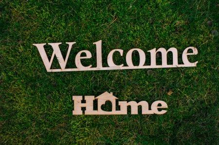Photo pour Lettres en bois Bienvenue chez vous sur l'herbe verte - image libre de droit