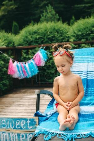 Photo for Cute little girl on a chair by the pool - Royalty Free Image