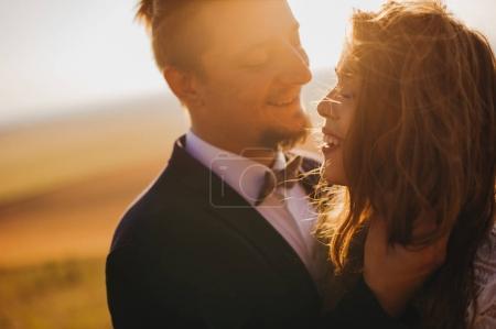 Photo pour Heureux jeune marié couple baisers en plein air - image libre de droit