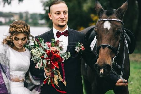 couple with a black horse