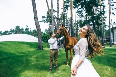 couple standing next to a horse