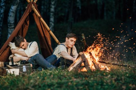 twin brothers sitting around a campfire