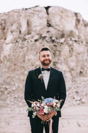 groom with a bouquet of flowers