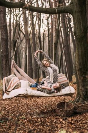 twin sisters on swing in forest