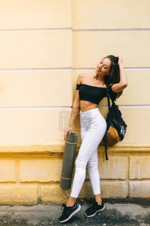 Beautiful youn woman with yoga mat...
