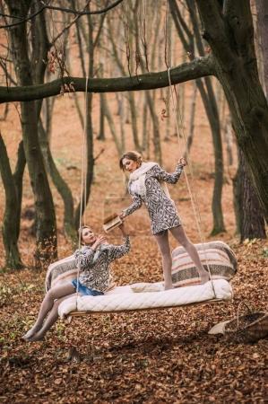 Photo pour Deux belles sœurs jumelles en balançoire dans la forêt d'automne - image libre de droit