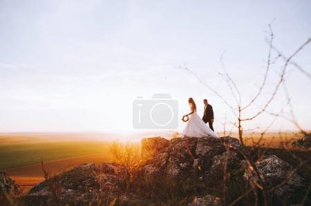 Photo pour Silhouette d'une jeune mariée et marié sur fond de coucher de soleil - image libre de droit