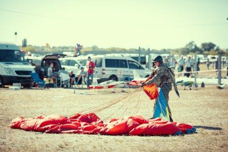 Photo pour Parachutiste avec parachute rouge après l'atterrissage au sol . - image libre de droit