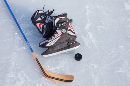 Hockey Stick and Puck on the Ice Rink.