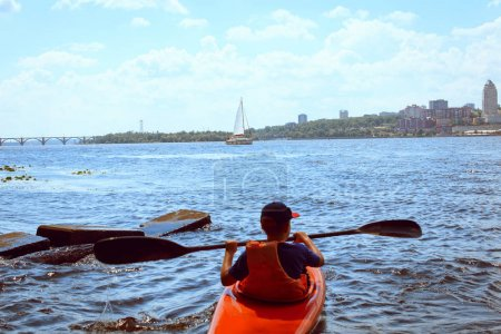 Photo for Man paddling in kayak is on a river, kayaking - Royalty Free Image