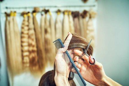 Photo pour Image recadrée de coiffeur coupe extrémités de cheveux blonds - image libre de droit