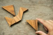 Man hold triangle to fulfill tangram puzzle in bird shape (Concept for freedom, free life or explore new world)
