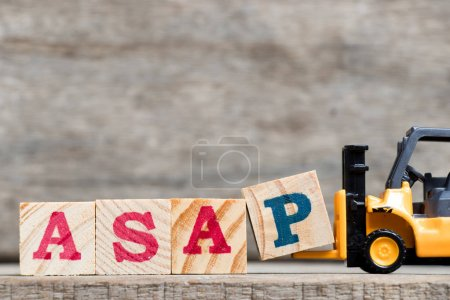 Yellow plastic forklift hold letter P to complete word ASAP (abbreviation of as soon as possible) on wood background