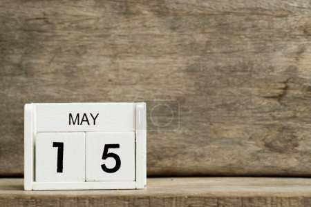 White block calendar present date 15 and month May on wood background