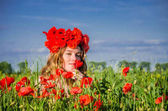 Young beautiful girl in a field of flowering poppies with a wreath of poppies on her head enjoying the aroma of a poppy flower