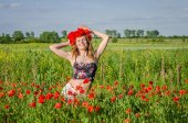 A young, happy, beautiful girl is having fun and dancing with joy in the field of flowering poppies with a wreath of poppy flowers on her head, a hot, sunny summer day