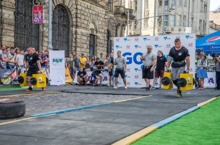 LVIV, UKRAINE - AUGUST 2017: A strong bodybuilder athlete lifts a huge steel heavy pipe to the strongman game in front of enthusiastic spectators