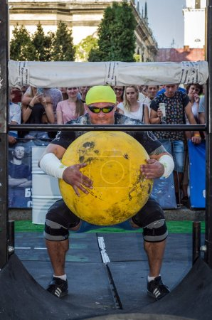 LVIV, UKRAINE - AUGUST 2017: A strong athlete a bodybuilder lifts a huge heavy stone yellow ball at Strongmen games